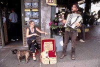 Couple performing in the street to get money for the orphan dog
